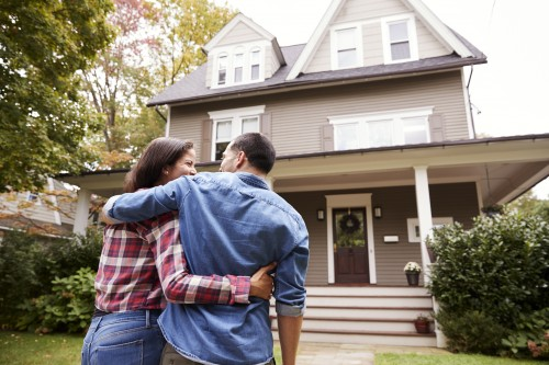 Homeowners hugging outside of their house.
