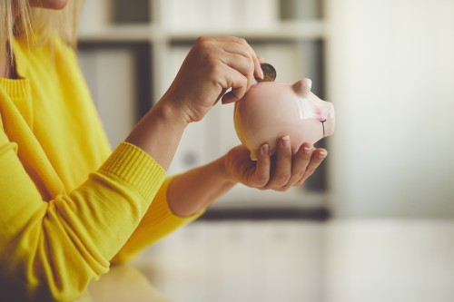 Woman wearing a yellow sweater putting money into a piggy bank.