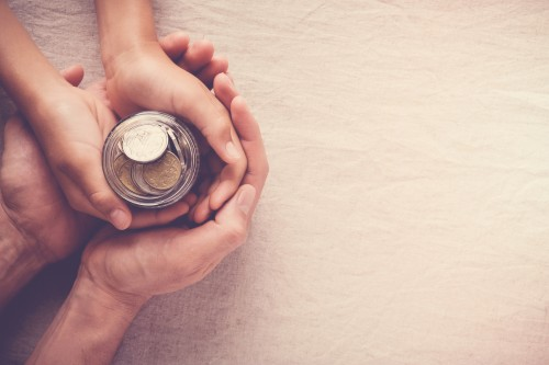 Adult hands holding child hands with a jar of money.