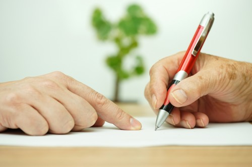 Close-up of hands and pen crafting a will.