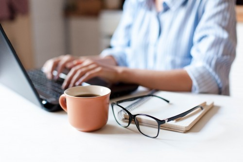 Person working from home on a laptop with a mug of coffee.